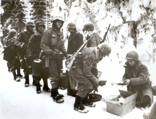 Chow is served to American soldiers on their way to Belgium. January 13, 1945.